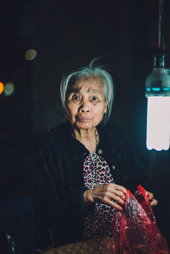 A old lady working during the night market in Hanoi Portrait Of A Woman Portraits Vietnam Vietnamese Adult Casual Clothing Females Front View Hairstyle Holding Indoors  Leisure Activity Lifestyles Looking At Camera Mature Adult Night Old Buildings One Person Portrait Real People Senior Adult Senior Women Waist Up Women