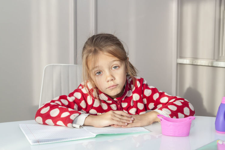 Portrait of girl sitting on table