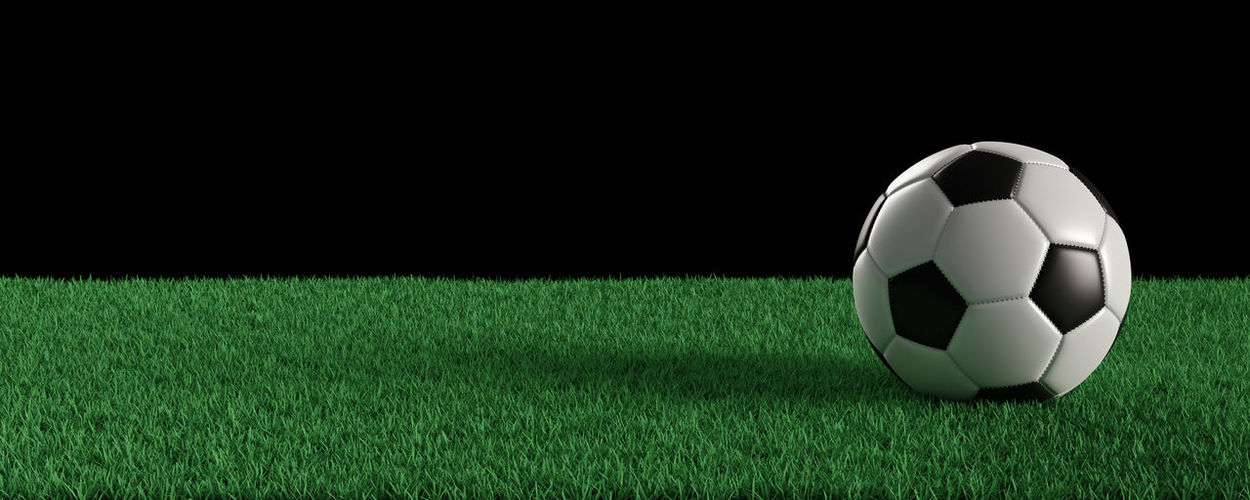 Close-up of ball on field against black background