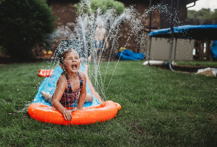 Childhood Child Enjoyment Girls Fun Playing Happiness Water Splashing Day Positive Emotion Emotion Mouth Open Spraying Smiling Outdoors Innocence Summer Slip And Slide