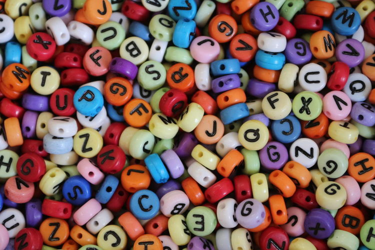Full frame shot of multi colored beads with alphabets
