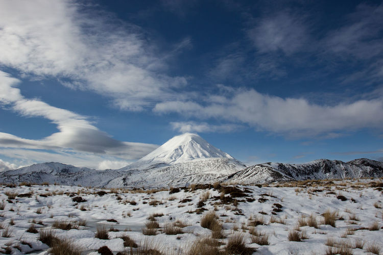 Lenticular clouds beside the snow covered mt ngauruhoe in the tongariro national park