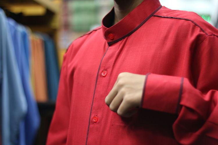 Midsection of boy wearing red shirt while standing in shop