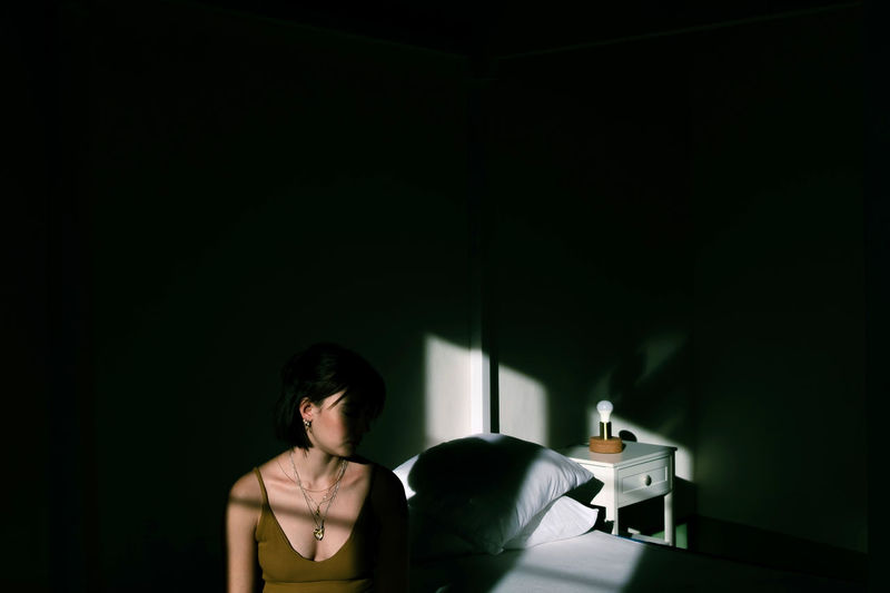 Woman sitting on bed in darkroom