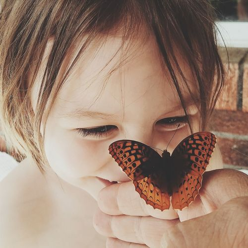 Close-Up Of Girl Looking At An Orange Butterfly