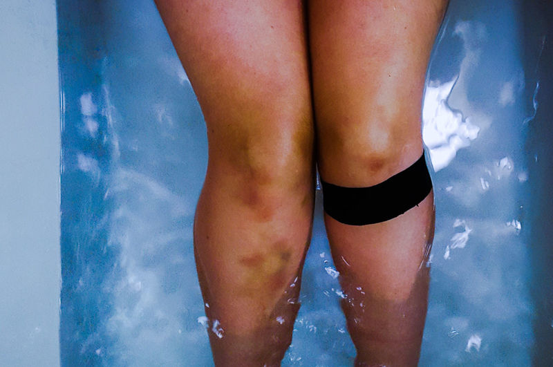 Low section of woman in swimming pool against sea