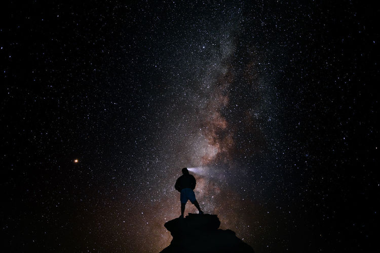 Silhouette Person Standing On Rock Against Star Field At Night