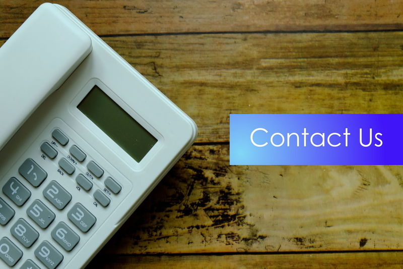 Contact Us Calculator Call Call Us Capital Letter Close-up Communication Connection Finance High Angle View Indoors  Information Message No People Number Sign Still Life Table Technology Telephone Text Western Script Wireless Technology Wood - Material
