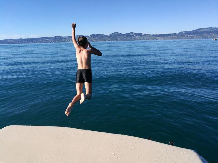 Full length of shirtless boy jumping in sea against clear sky