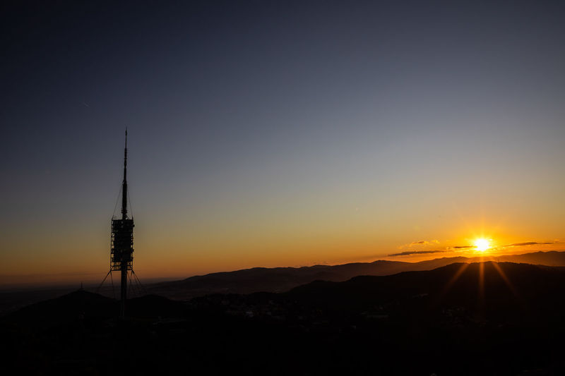 Silhouette of tower against sky during sunset