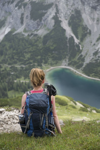 Rear view of backpack woman sitting on mountain