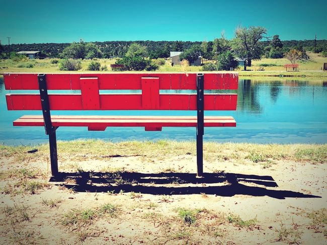 """""""A Day On The Pond"""" Lonely reflection, lonely soul, seeking a destination, no where to go. Shadow New Mexico Photography New Mexico Introspection Bench Park Bench Pond Alone Lonely Water Sky Day No People Red Absence"""