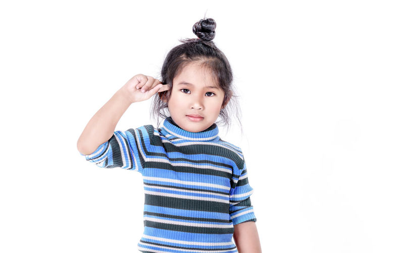 Portrait of cute girl standing against white background