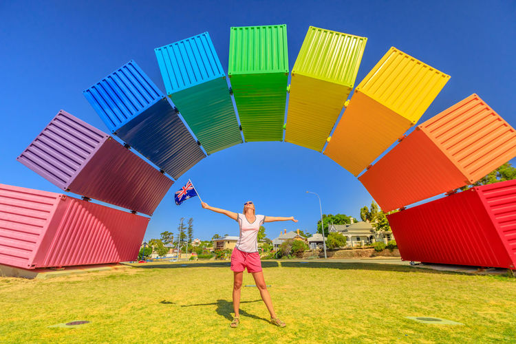 Happy woman with open arms looking Rainbow Sea Container in Fremantle, Western Australia. Female tourist enjoys at Fremantle welcome. Homosexuality and hope concept Freemantle Perth Perth Australia Western Australia Australia Australian Rainbow Bridge Colorful Rainbow Colors Rainbow🌈 Blue Sky Woman Homosexual Love Pink Color Girl Females Happy Happyness Day One Person Sky Real People Multi Colored Human Arm Leisure Activity Nature Grass Land Architecture Clear Sky Limb Lifestyles Standing Blue Full Length Built Structure Casual Clothing Arms Raised Human Limb