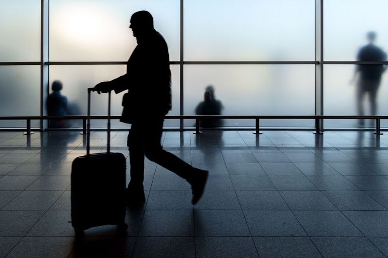 Silhouette Man With Luggage Walking At Airport
