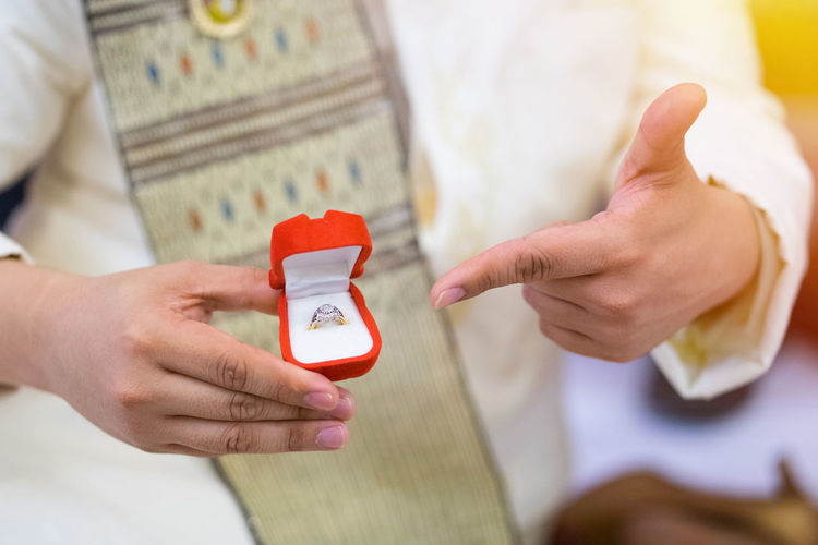 Midsection Of Bridegroom Holding Wedding Ring During Ceremony