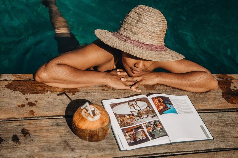 Hat One Person High Angle View Water Clothing Relaxation Real People Holiday Vacations Sunlight Sun Hat Leisure Activity Wood - Material Trip Nature Outdoors Beach Day Land Straw Hat