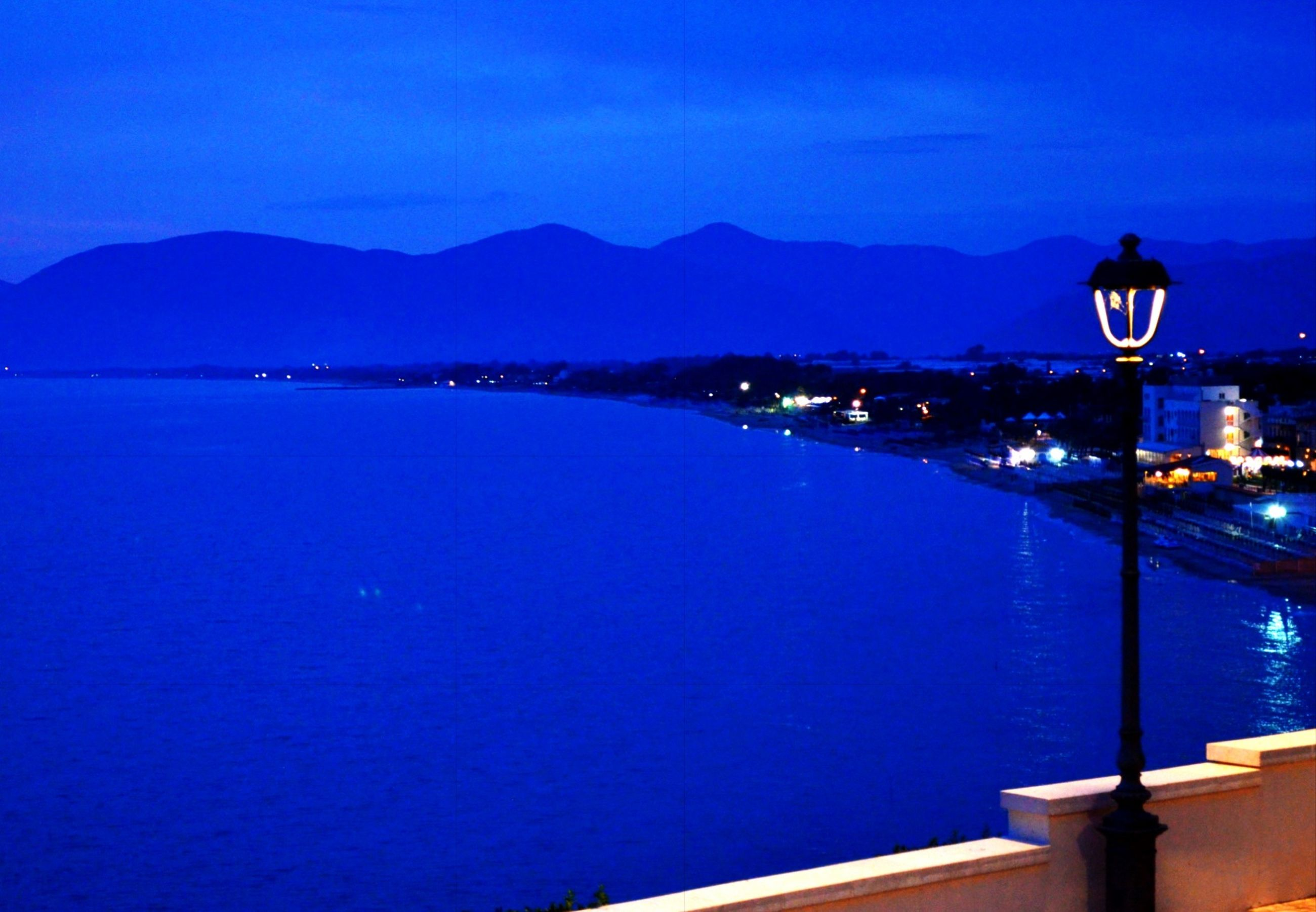 blue, water, mountain, sea, built structure, illuminated, architecture, clear sky, building exterior, mountain range, transportation, nautical vessel, night, copy space, city, river, nature, scenics, outdoors, sky