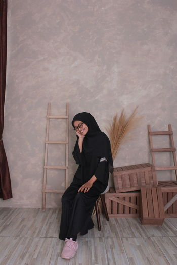 Full length of smiling woman in burka sitting on wooden chair