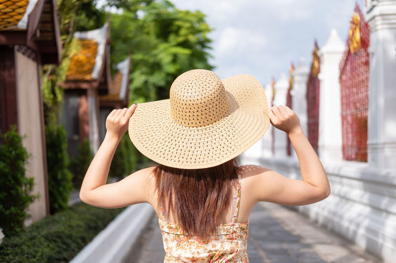 Rear view of woman wearing hat while standing on footpath