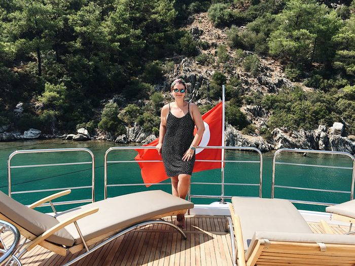 Woman standing by turkish flag in boat on sea