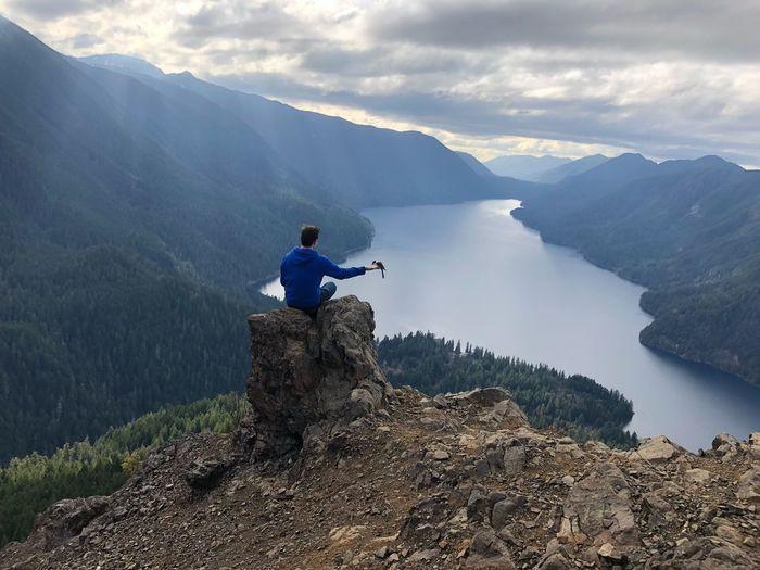 Man sitting on rock while feeding bird