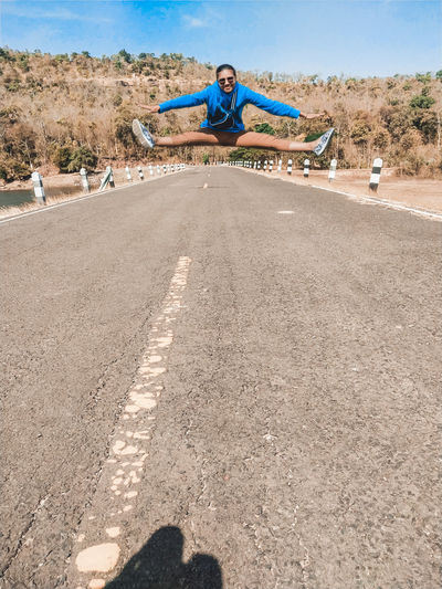 Man jumping in mid-air on road against trees