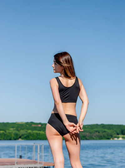 Girl in shorts and sports bra in sport on the dock at the lake.