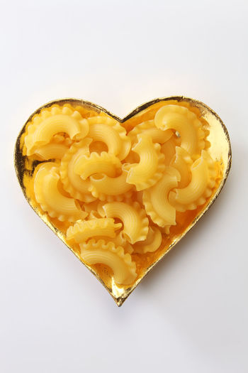 creste di gallo pasta in the heart shape container Dried Food Food And Drink Love Meal Noodles Wheat Creste Di Gallo Directly Above Food Gold Colored Healthy Eating Heart Shape High Angle View Italian Culture Italian Food No People Nutrition Pasta Positive Emotion Raw Food Spahgetti Still Life Studio Shot White Background Yellow