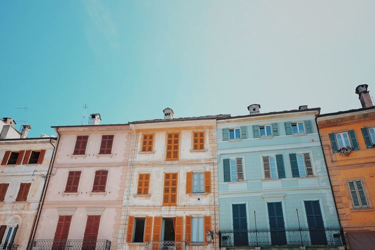 Bright buildings in an old Italian town. Architecture Bright Buildings Building Exterior Built Structure Clear Sky Colourful Buildings Day Low Angle View Nature No People Old Buildings Outdoors Perching Sky Window