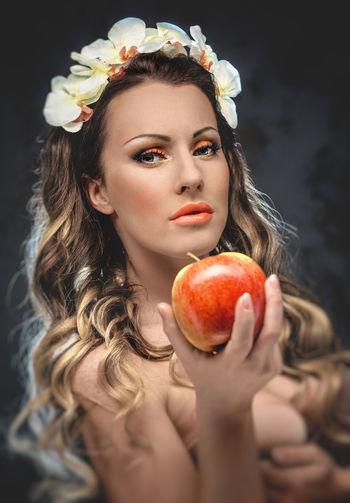 Close-up portrait of seductive woman holding apple