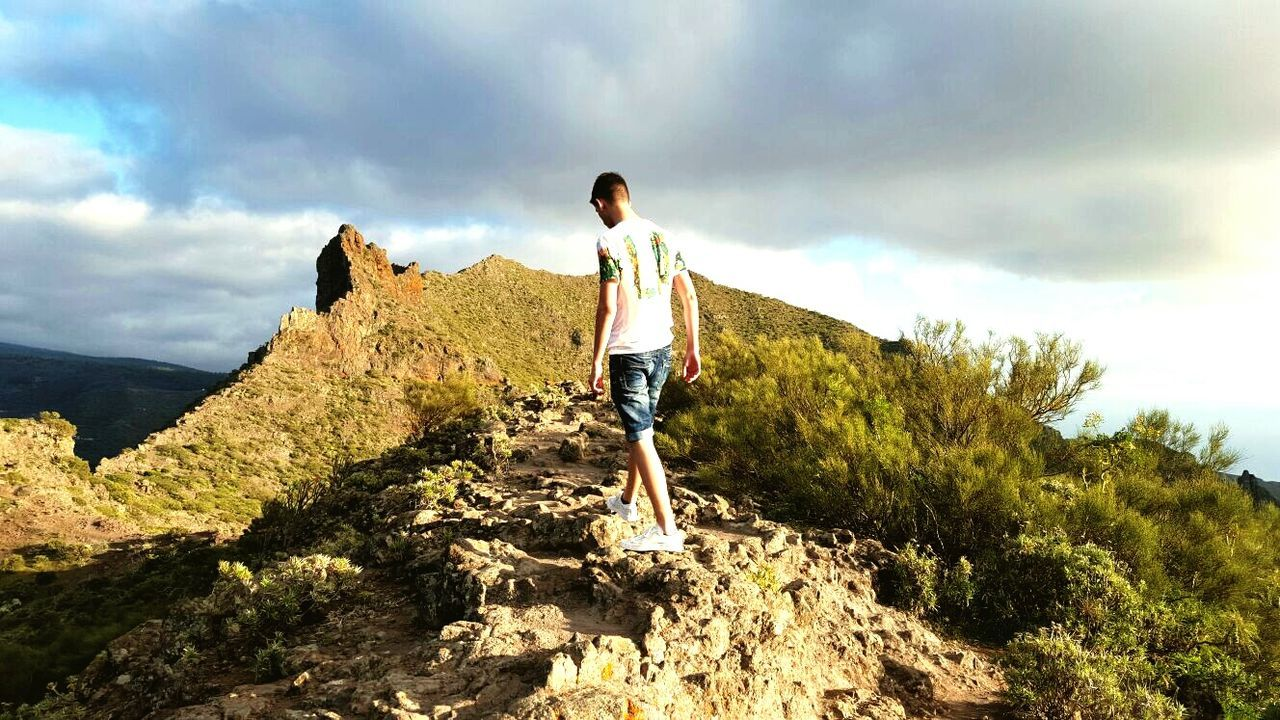 real people, full length, leisure activity, nature, lifestyles, sky, rock - object, cloud - sky, rear view, one person, mountain, scenics, casual clothing, beauty in nature, day, landscape, hiking, outdoors, men, adventure, standing, tree, young adult, people