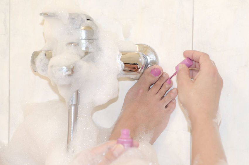 Woman painting her toenails in pink in the bathtub Adults Only Applying Beauty Body Care Color Domestic Bathroom Enjoyment Fingernail Foam Human Body Part Human Foot Human Hand Indoors  Lifestyles Nail Polish One Person One Woman Only Only Women Painting People Personal Perspective Pink Color Relaxation Toenail Women