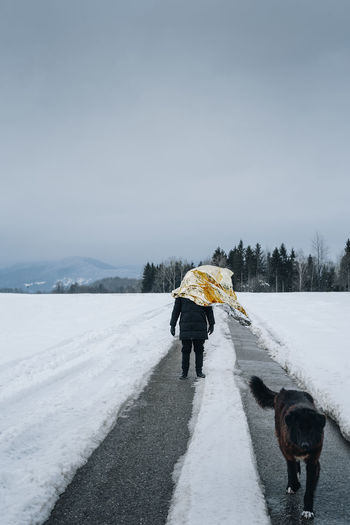 Dog walking on road by man with foil amidst snowy landscape against sky
