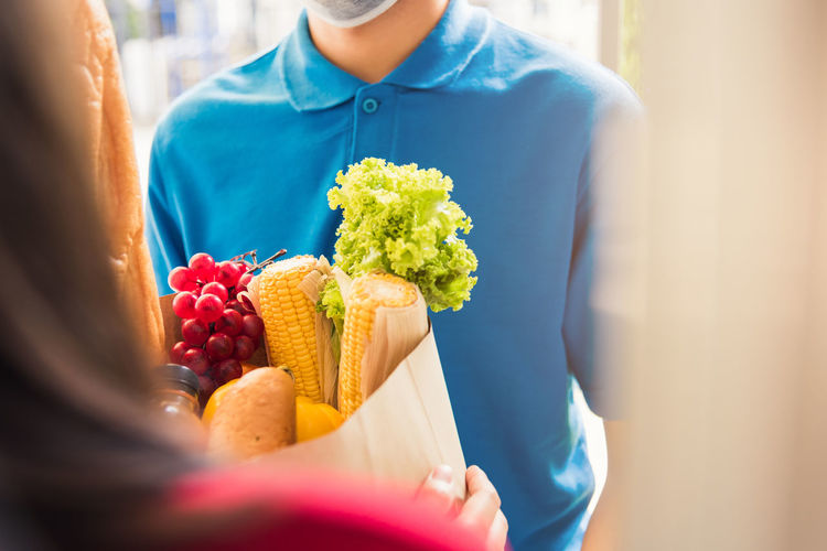 Asian young delivery man in uniform wear protective face mask he making grocery