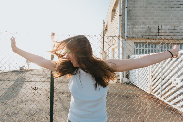 Woman with arms outstretched standing against built structure