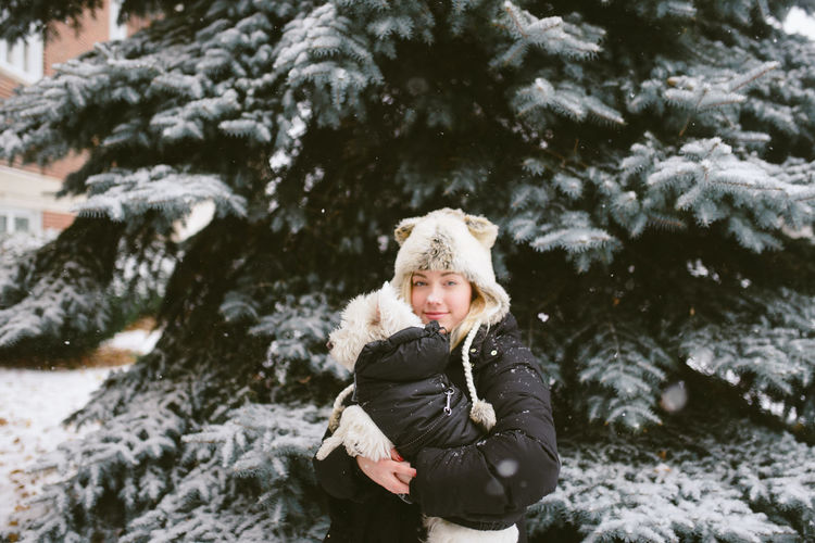 Portrait of woman carrying dog while standing against tree during winter