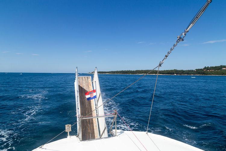 Sailboat sailing in sea against blue sky