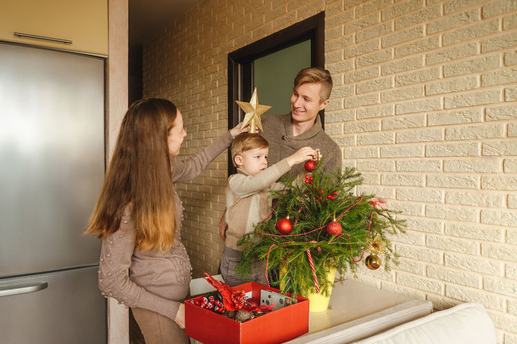 Family decorating the christmas tree against wall
