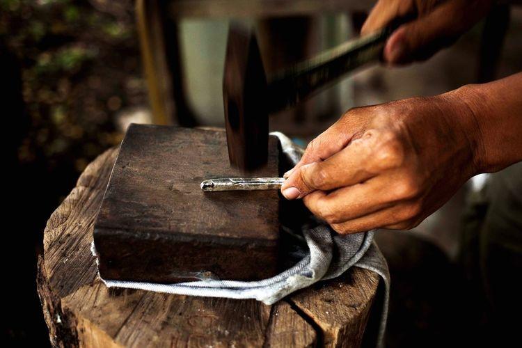 Cropped hand hammering on metal in workshop