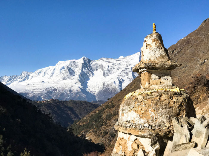 Everest Base Camp Trek - Buddhist stupa in front of snow covered mountain range near Pangboche Himalayas Stupa Beauty In Nature Everest Base Camp Trek Mountain Peak Mountain Range No People Snowcapped Mountain