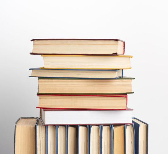 Stack of books on table against white background