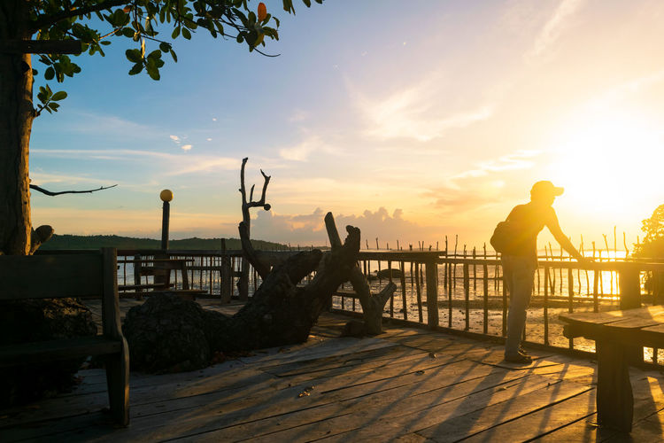 Man Wood - Material Lifestyles Wooden Landscape Perspective Outdoors Seascape Golden Hour Sundown Water Sea Sunset Tree Beach Silhouette Summer Sunlight Men Pier Jetty Footbridge Wood Paneling Bridge - Man Made Structure Knotted Wood Covered Bridge Observation Point Countryside Calm Arch Bridge