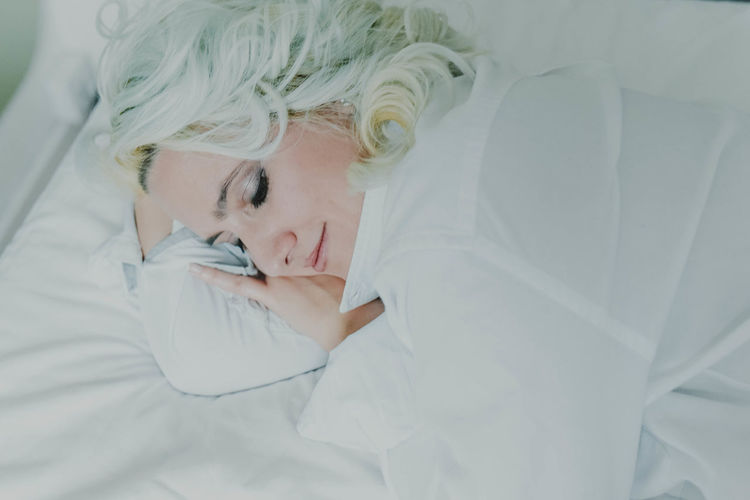 High angle view of young woman sleeping on bed
