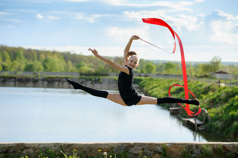 Acrobat Blonde Caucasian Cheerful Flexible Girl Gymnastics Horizontal Leg-split Outdoor Performance Pond Rhythmic Ribbon Skills  Sport Stretching Summer Training Water