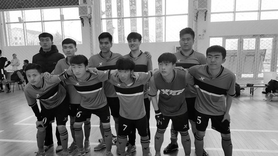 Full length of soccer team standing in court