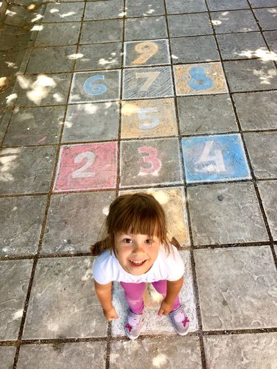 High angle portrait of girl playing hopscotch