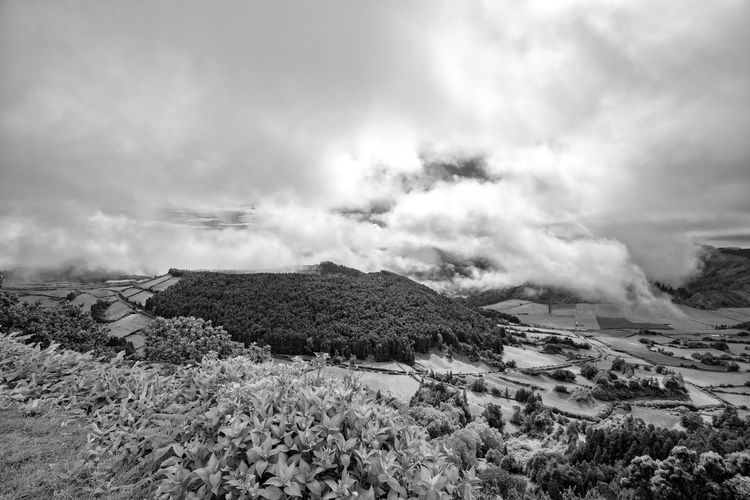 Black and white view of the dramatic clouds over the Caldera of Alferes near the town of Sete Cidades in Sao Miguel. Sete Cidades Azores Azorean Açores Sao Miguel Crater Caldera Caldeira Alferes Village Lagoa Azul Verde Clouds Farm Pasture Hike View Landscape Tourism Trek Volcano Black And White