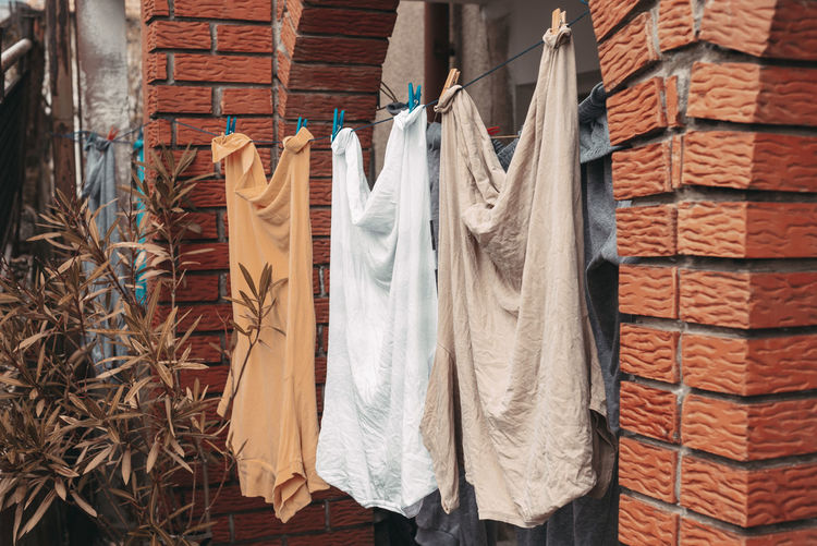 Clothes drying against brick wall