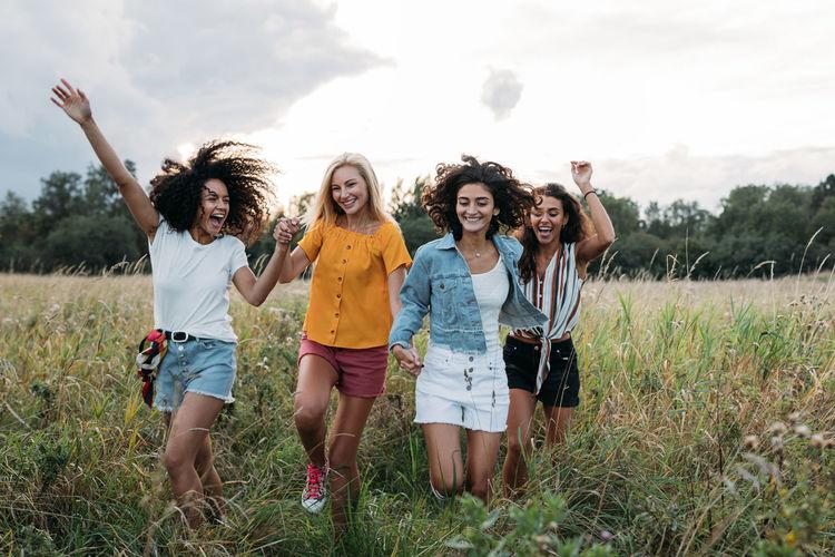 Portrait of happy friends standing on field against sky